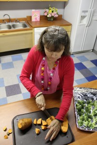 Nancy Schaeffer chopping sweet potato; image courtesy of DCT